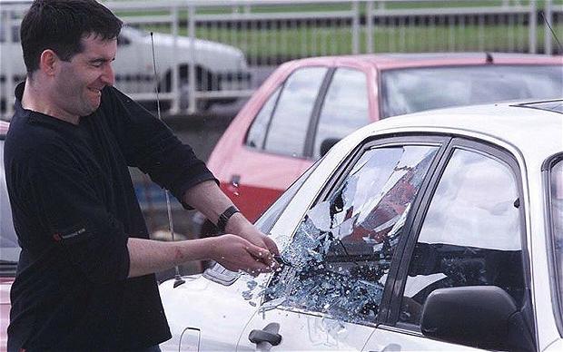 Мужчина разбивает стекло